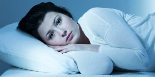 Troubled young woman in bed and lack of sleep