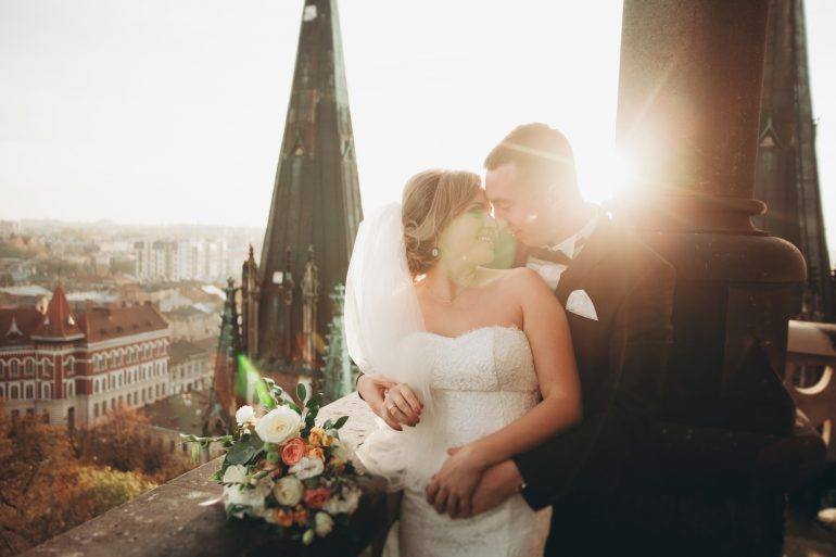 Stylish beautiful wedding couple kissing and hugging on background panoramic view of the old town.
