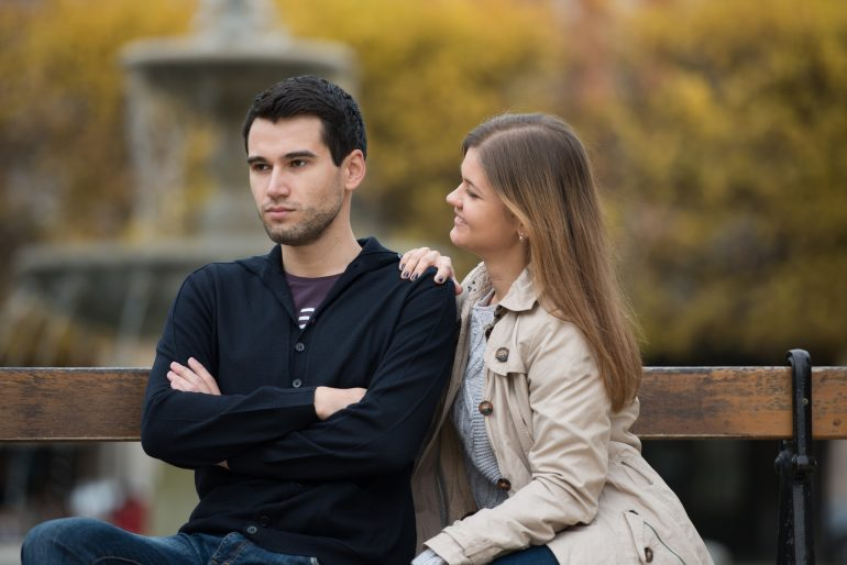 young couple having romantic conversation after love fight on the bench in park in Paris, France