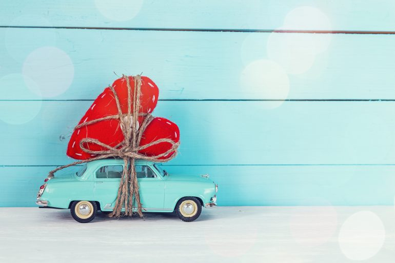 Background with miniature blue toy car carrying a heart on blue painted wooden planks. Place for text.