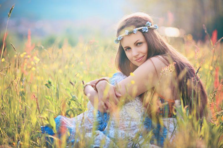 Beautiful romantic woman in flower field . Hippie and gypsy dress