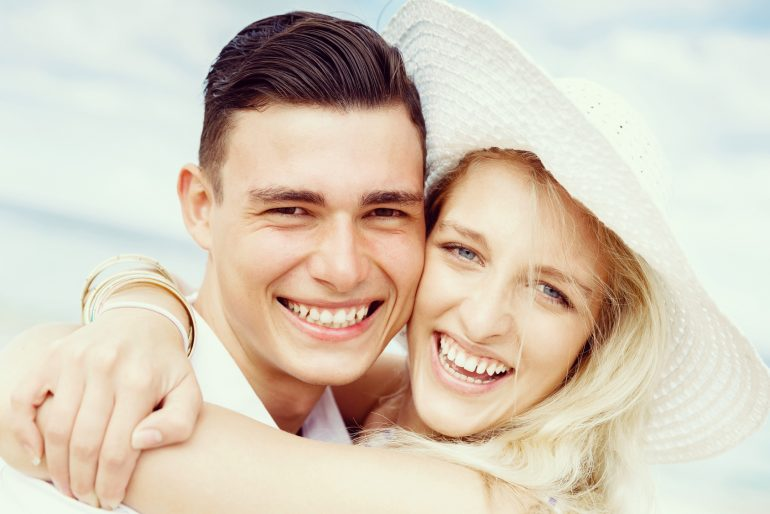Portraits of romantic young couple on the beach