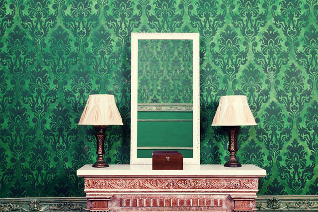 Mirror on fireplace next to two vintage chandeliers in retro styled room. Green vintage interior. Royal architecture