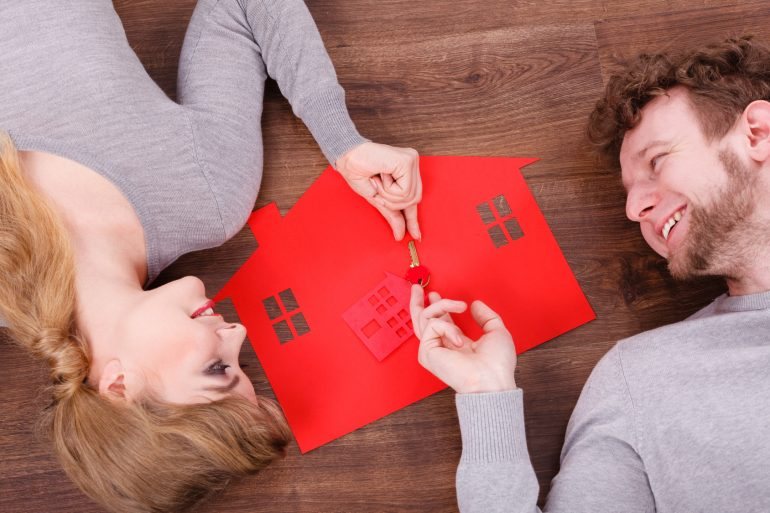 Home security safety future family mortgage finances concept. Young couple exchanging keys. Man and wona lying on floor with house cutout.