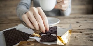 Woman is eating a chocolate bar and coffee