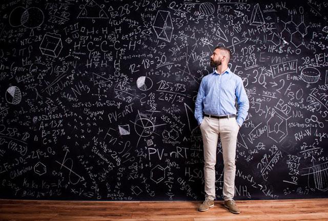 Hipster teacher standing against big blackboard with mathematical symbols and formulas. Studio shot on black background.