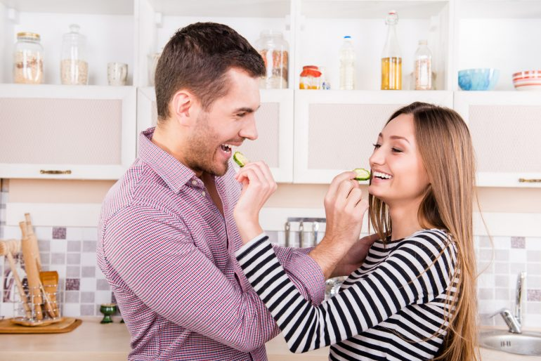 Cheerful couple in love feeding each other with cucumber, close up portrait