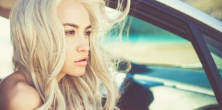 Atmospheric outdoors fashion portrait of beautiful blonde in car on the beach