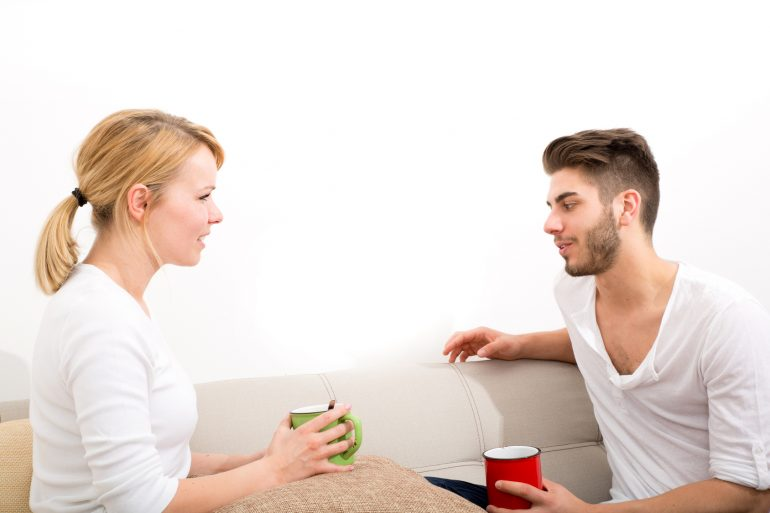 A young couple talking with coffee on the Sofa.