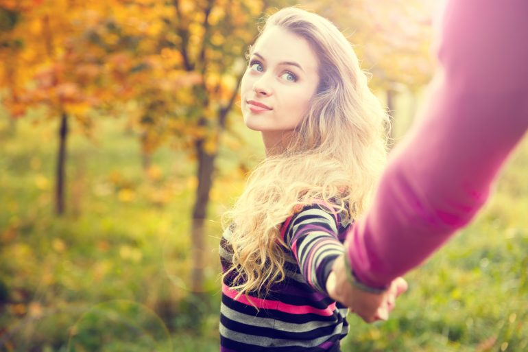 Young Woman Holding Hands on Autumn Background in Sunny Day. Toned Photo with Lens Flare Effect and Copy Space.