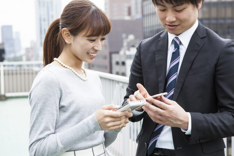 Men and women are watching the mobile phone on the roof