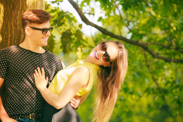 Love and happiness. Young happy couple lovers wearing sunglasses dating in summer park outdoor.