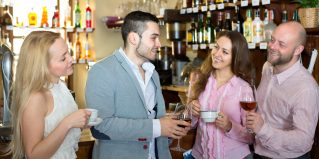 Two beautiful couples having a night out in a bar drinking spirits and coffee