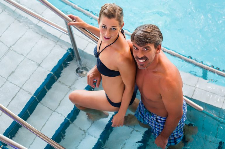 Couple on steps of pool in thermal spa getting out of the water