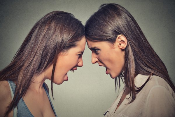 Two women fight. Angry women screaming looking at each other