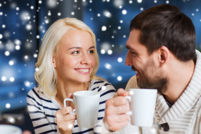 people, leisure, communication and season concept - happy couple meeting and drinking tea or coffee at winter cafe