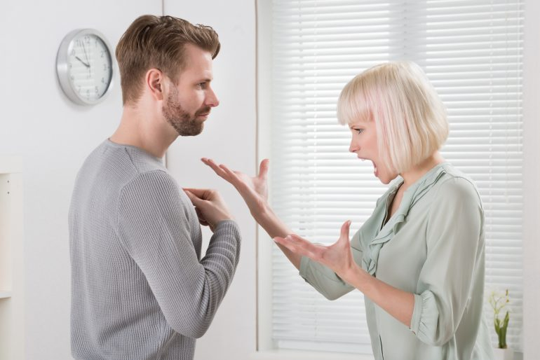 Unhappy Young Couple Arguing With Each Other At Home